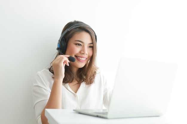 La donna asiatica sulla camicia bianca parla con la cuffia e usando il concetto felice dell'operatore del computer portatile, di sorriso e del fronte