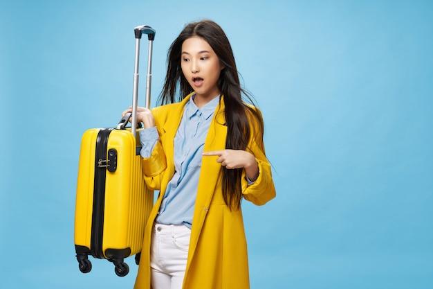 La donna asiatica viaggia con una valigia in sue mani, concetto di vacanza
