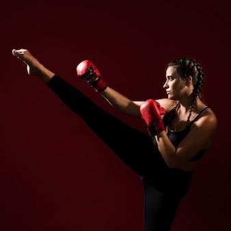 La donna atletica in forma fisica copre dare un calcio