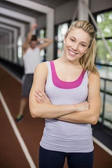 La donna atletica sorridente che posa con le armi ha attraversato sulla pista