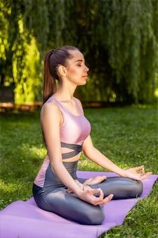 La donna atletica sorridente sta facendo l'yoga