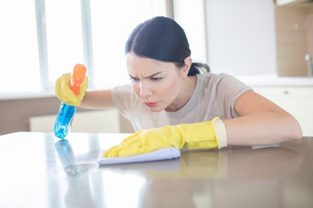 La donna attenta e concentrata sta spruzzando sulla superficie del tavolo e la pulisce con uno straccio. lei lo guarda molto seriamente. bruna indossa guanti gialli.
