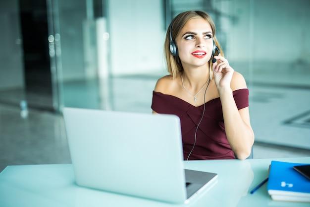 La donna attenta focalizzata in cuffie si siede alla scrivania con il laptop, guarda lo schermo, prende appunti, impara la lingua straniera su internet, il corso di studio online per l'autoeducazione sul web consulta il cliente tramite video