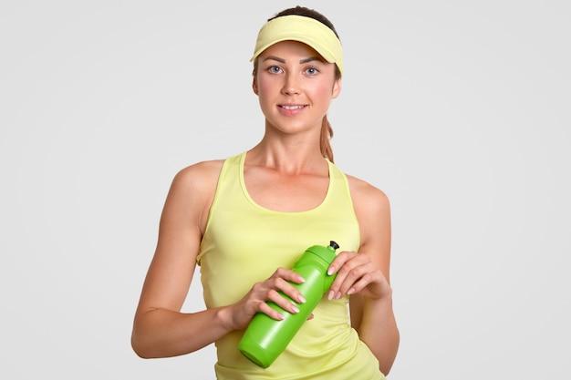 La donna attiva assetata fa una pausa dopo aver giocato a tennis, vestita in abbigliamento sportivo casual, tiene la bottiglia con acqua, si trova sola contro il bianco. concetto di persone, sport e stanchezza