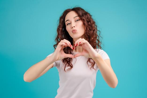 La donna attraente che mostra il cuore modella con le sue mani isolate sopra fondo del turchese