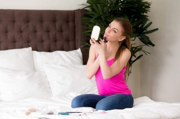La donna attraente fa il trucco quotidiano del mattino a casa