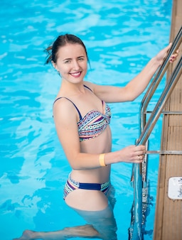 La donna attraente in costume da bagno sta uscendo della piscina, sta esaminando la macchina fotografica e sta sorridendo. bellissimo sfondo di acqua turchese