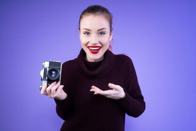 La donna attraente in maglione lavorato a maglia ci mostra la sua nuova macchina fotografica