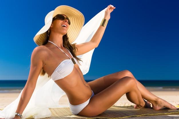 La donna attraente in un bikini sorride al sole alla spiaggia