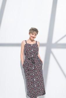 La donna attraente in un vestito scuro propone su una priorità bassa bianca astratta