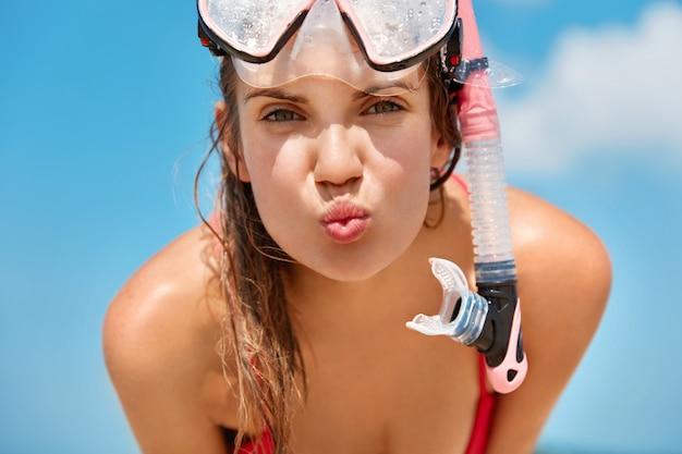 La donna attraente indossa la maschera da sub, nuota nell'oceano o nel mare, ama le immersioni, gode delle vacanze estive, posa contro il cielo blu