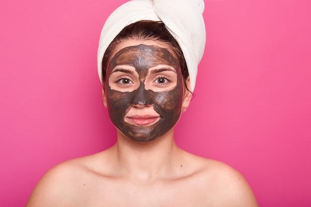 La donna attraente si pone con un'espressione facciale seria e calma, ha una maschera di cioccolato sul viso, con spalle nude, si prende cura della sua bellezza e del suo aspetto, indossa un asciugamano bianco sulla testa. concetto di cura della pelle.