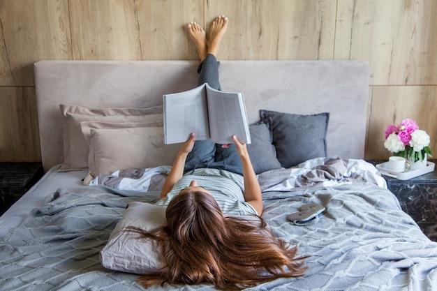 La donna attraente si trova sul letto la mattina, beve caffè, legge un libro, stile casual, vestito grigio, sentirsi a proprio agio a casa, riposarsi, sorridere