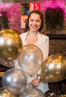 La donna attraente sorridente che tiene l'argento balloons nel partito