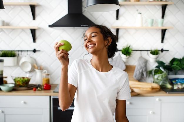 La donna attraente sorridente del mulatto si sta preparando a mordere una mela e sta osservando la mela sulla cucina moderna bianca