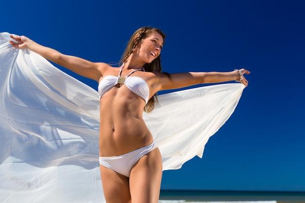 La donna attraente sta al sole sulla spiaggia