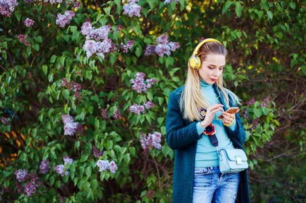 La donna attraente sta ascoltando musica e sta scrivendo sul suo telefono all'aperto nel parco tra i fiori lilla.