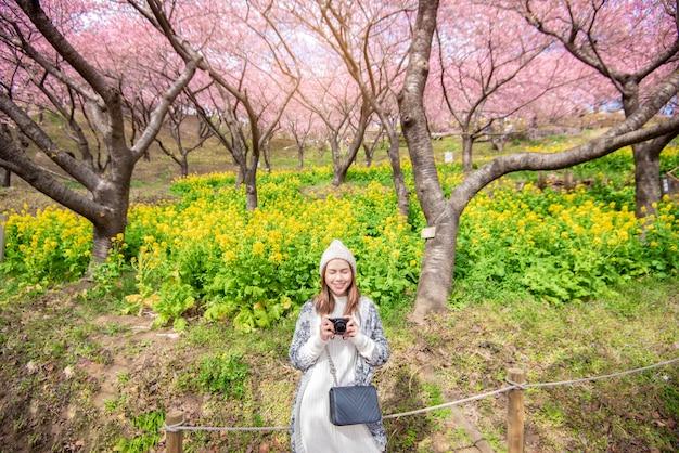 La donna attraente sta godendo con cherry blossom nel parco