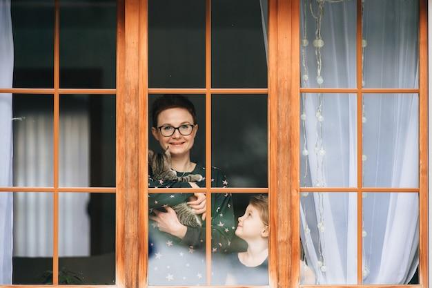 La donna bella con il gattino in mani osserva attraverso la grande finestra con la sua piccola bella figlia