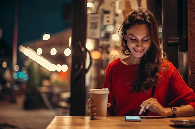 La donna beve il caffè e usa lo smartphone nella caffetteria