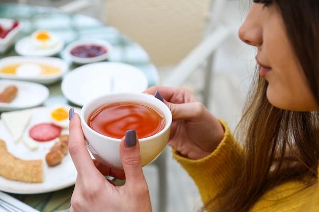 La donna beve il tè nero mentre la vista del primo piano della prima colazione