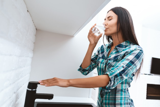La donna beve l'acqua dal vetro. mano su un rubinetto.
