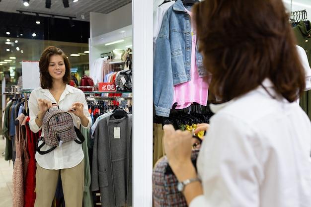 La donna bianca attraente con il bello sorriso tiene lo zaino in sue mani ed esamina la riflessione in specchio del camerino