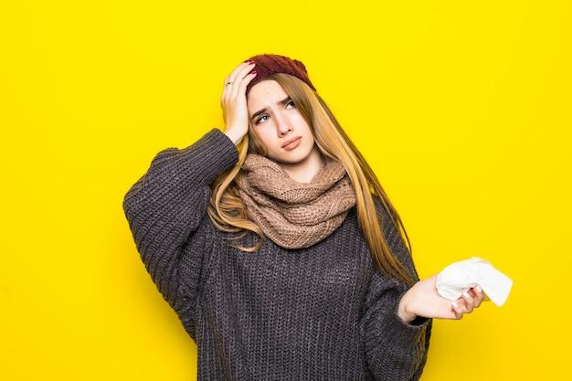 La donna bionda attraente in maglione caldo ha mal di testa e cerca di riscaldarsi
