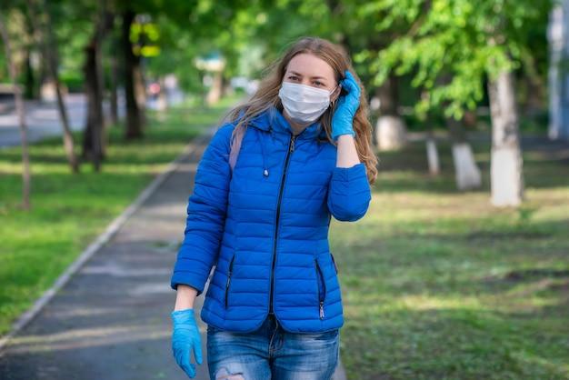 La donna bionda caucasica in maschera protettiva e guanti sta camminando lungo la strada vuota. stile di vita e comportamento sicuro durante una pandemia di coronavirus.