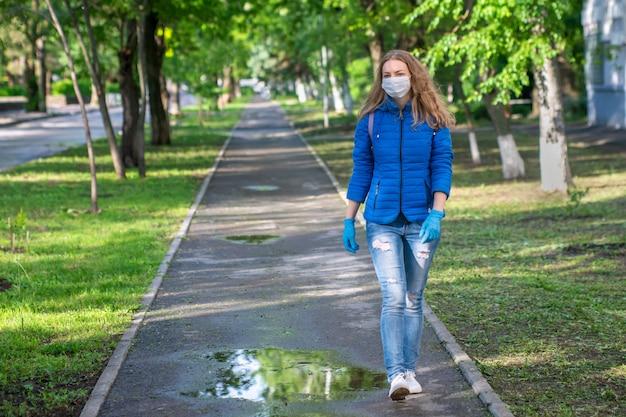 La donna bionda caucasica in maschera protettiva e guanti sta camminando su svuota la strada. prevenzione dell'infezione virale.
