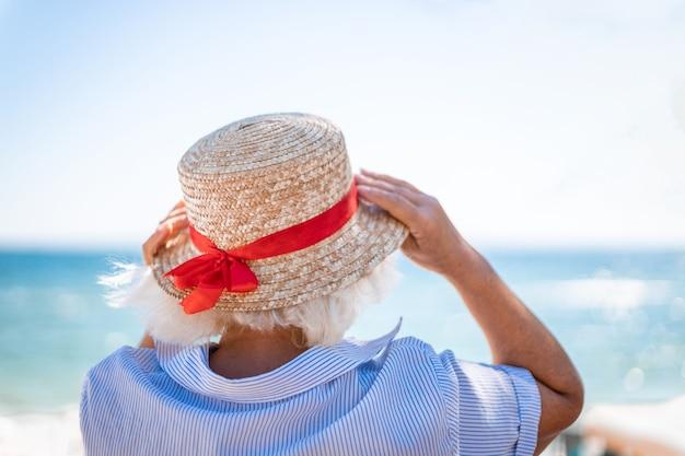 La donna bionda caucasica in un cappello di paglia con la schiena fa il segno di amore con le sue mani sul mare blu