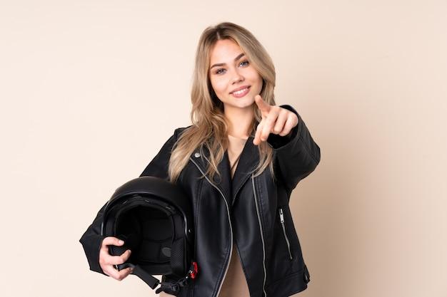 La donna bionda con un casco del motociclo isolato sulla parete beige indica il dito con un'espressione sicura