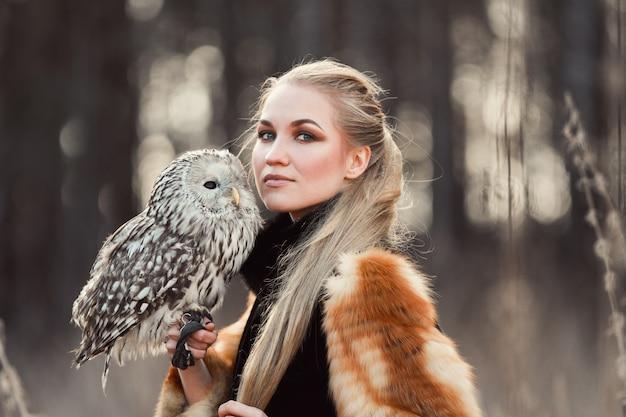 La donna bionda con un gufo in mano cammina nei boschi in autunno e primavera. donna capelli lunghi, ritratto romantico con gufo. foto di moda d'arte, bellissimo trucco