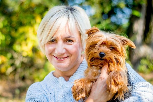 La donna bionda con un sorriso magico tiene in braccio un cagnolino