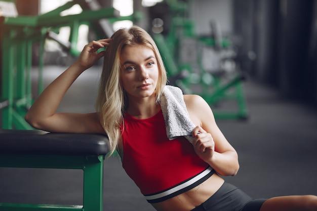 La donna bionda di sport in un abbigliamento sportivo ha un periodo di riposo in una palestra