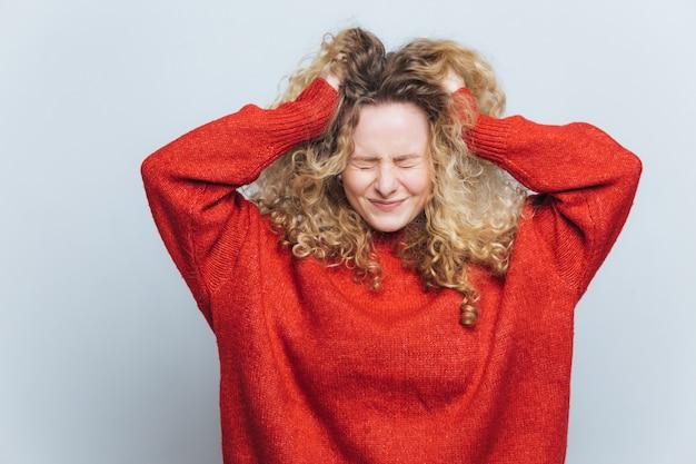 La donna bionda frustrata stressante si strappa i capelli, si rammarica di aver sbagliato