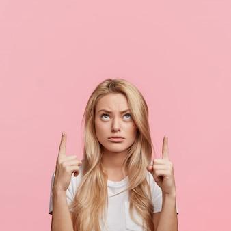 La donna bionda graziosa scontenta indica con le dita anteriori sopra la testa allo spazio vuoto della copia, guarda con sconcerto verso l'alto come dimostra qualcosa di strano, isolato sopra il muro rosa