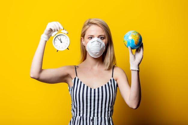 La donna bionda in maschera e guanti tiene la sveglia e il globo della terra