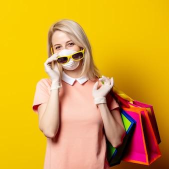 La donna bionda in maschera e vestito rosa tengono i sacchetti della spesa sulla parete gialla