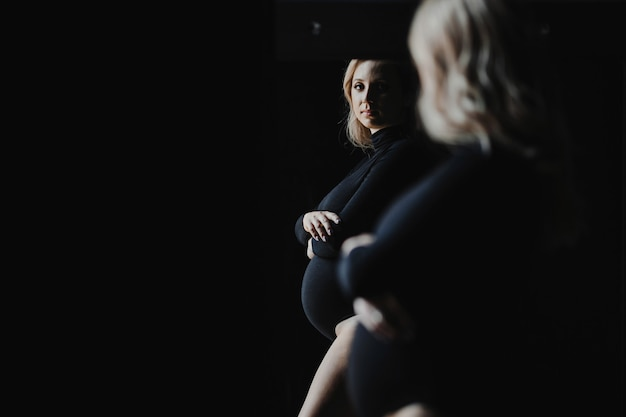 La donna bionda incinta in una tuta nera sta vicino ad uno specchio e esamina il suo riflesso