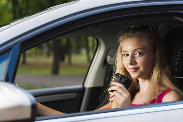 La donna bionda posa con la tazza di carta in automobile