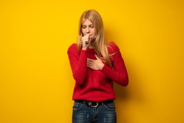 La donna bionda sopra la parete gialla sta soffrendo con la tosse e ritenendo cattiva