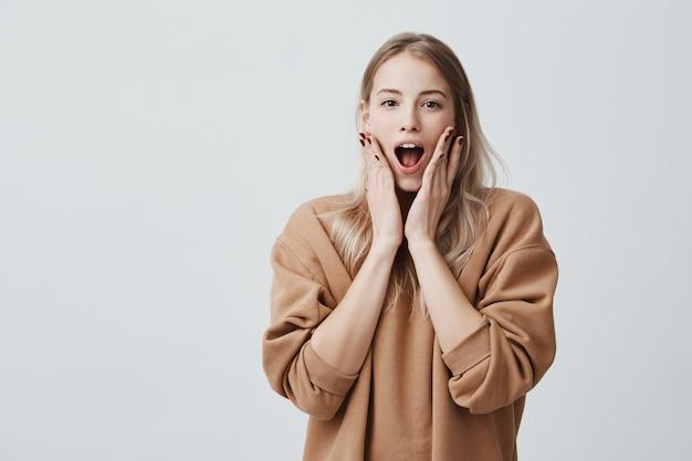 La donna bionda stordita stordita tiene la bocca ampiamente aperta