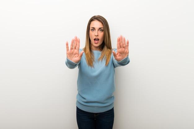 La donna bionda su fondo bianco isolato che fa il gesto di arresto per deludente con un parere
