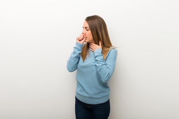 La donna bionda su fondo bianco isolato sta soffrendo con la tosse e ritenendo cattiva