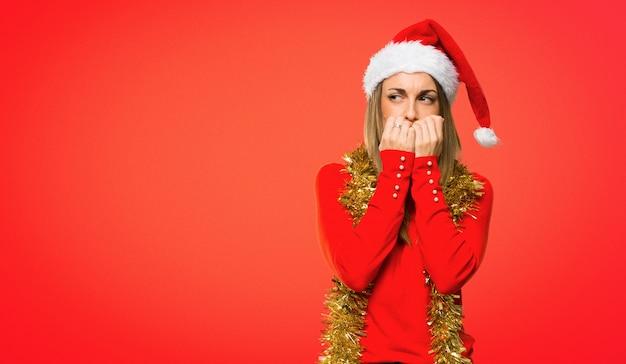 La donna bionda vestita per le vacanze natalizie è un po 'nervosa