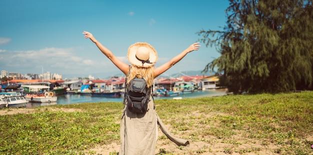 La donna bionda viaggiatore con zaino e sacco a pelo del viaggiatore nella vista posteriore del cappello di paglia cammina lungo la costa ai pescherecci del molo. avventura di viaggio in cina. turistica isola tropicale dell'asia. concetto di viaggio vacanza vacanze estive