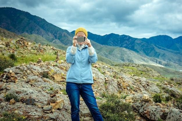 La donna blogger decolla foto e video dallo smartphone sulle montagne e sul cielo nuvoloso. viaggiare lifestyle tecnologia moderna.