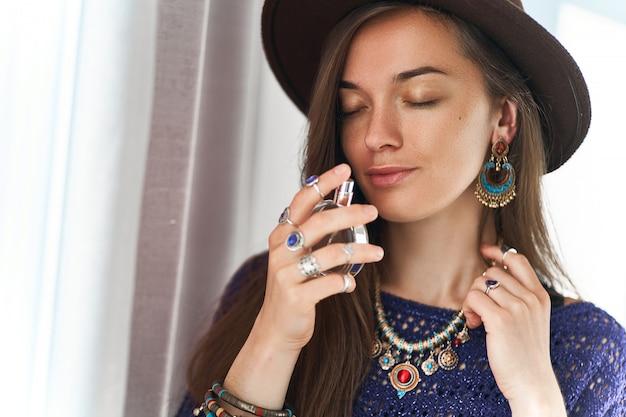La donna boho chic castana sensuale alla moda attraente alla moda con gli occhi chiusi che indossa gioielli e cappello gode del profumo del profumo