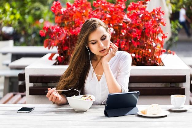 La donna bruna guarda qualcosa sulla sua tavoletta mentre si siede nel ristorante
